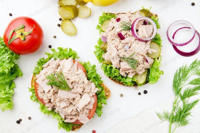 Flacher Blick auf Thunfisch-Sandwiches mit Salat Tomaten Gurken und Zwiebeln auf Pergamentpapier