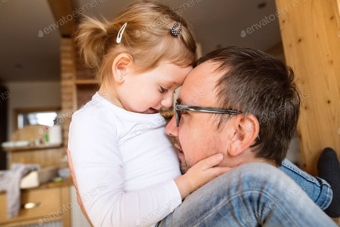 Young father with his cute little daughter at home.