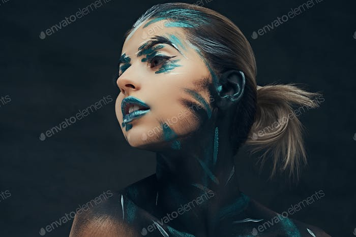 A young sensual girl with creative makeup. Blue and black shadows painted on her face.