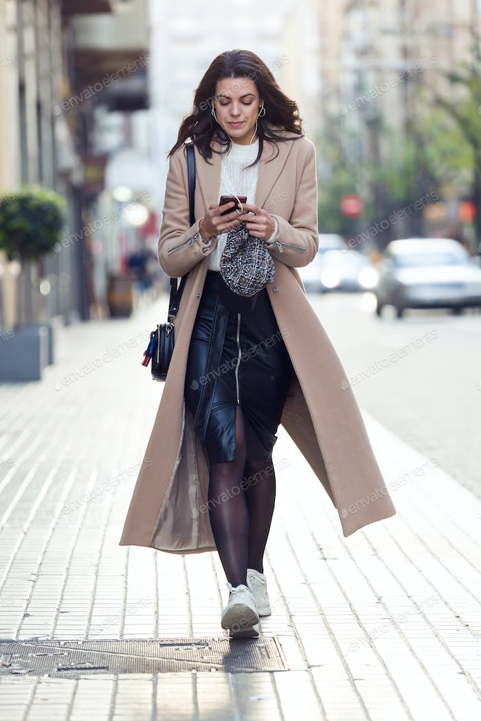 Pretty young woman listening to music with her mobile phone while walking in the street.