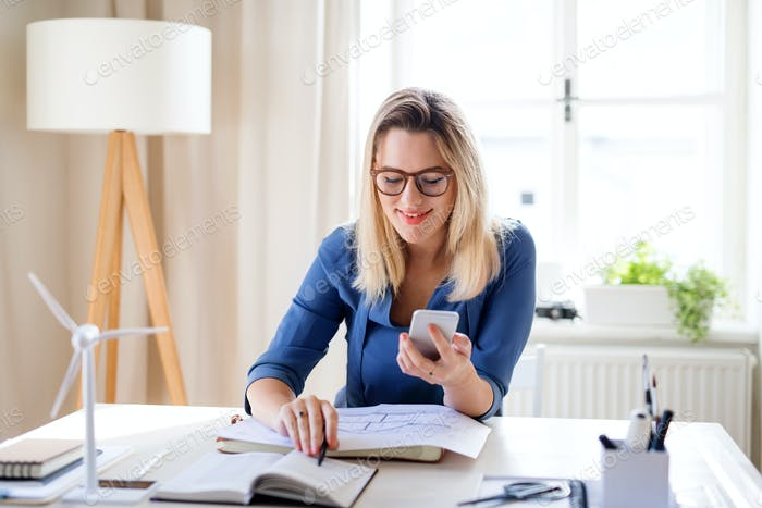 Young woman architect sitting at the desk indoors in home office, working.