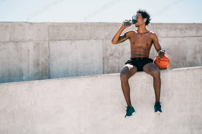 Athletic man drinking water after work out outdoors.