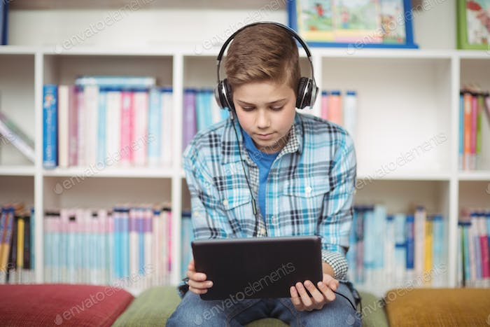 Attentive schoolboy listening music while using digital tablet in library