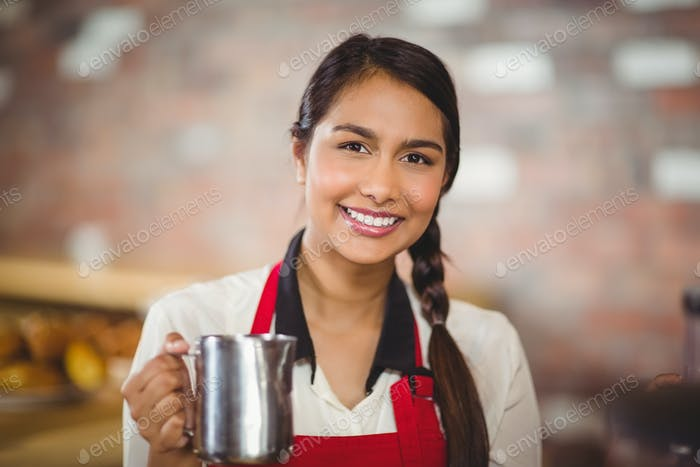 Portrait of a barista holding a milk jug at the coffee shop