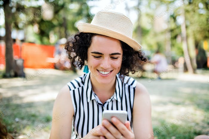 Young woman at summer festival or camping holiday, using smartphone
