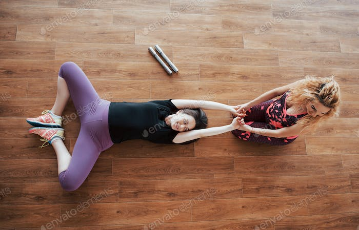 Pregnant woman doing yoga with personal trainer