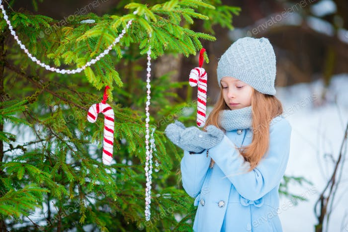 Portrait of a little cute smiling girl in a blue coat and mittens standing near the decorated