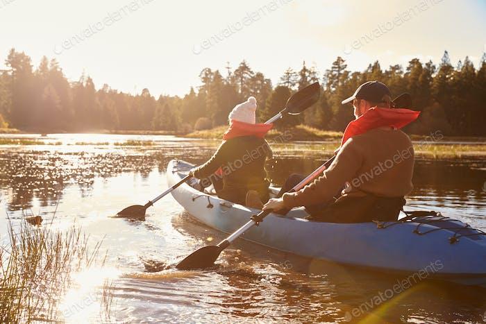 Couple kayaking on lake, back view, close-up