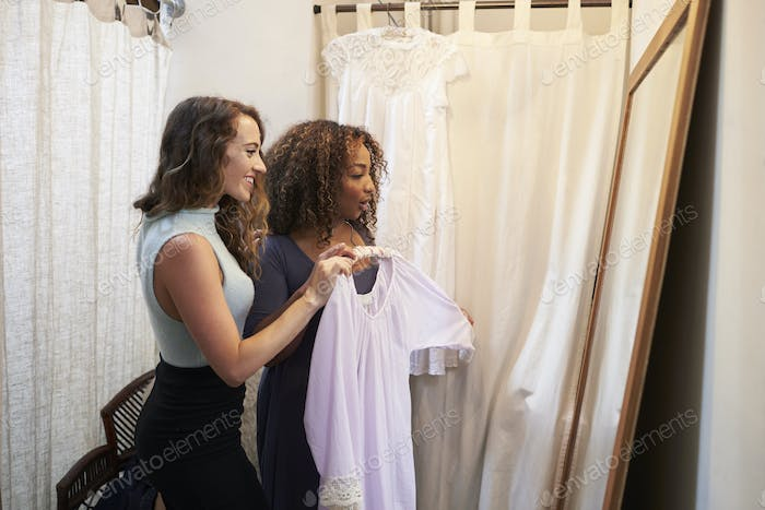 Woman in boutique changing room with friend holding a dress