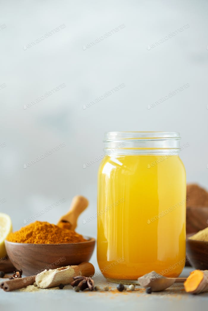 Ingredients for orange turmeric drink on grey concrete background. Lemon water with ginger, curcuma