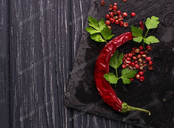 Chili peppers and rose pepper on slate background