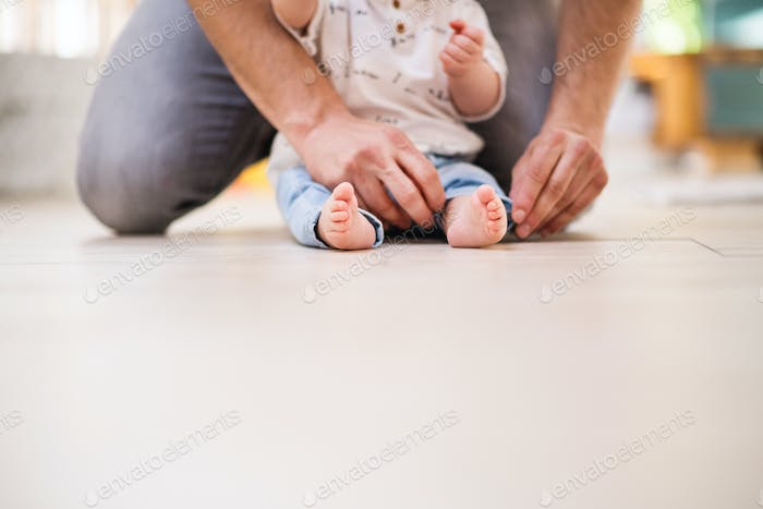 Unrecognizable father with a baby son at home. Copy space.