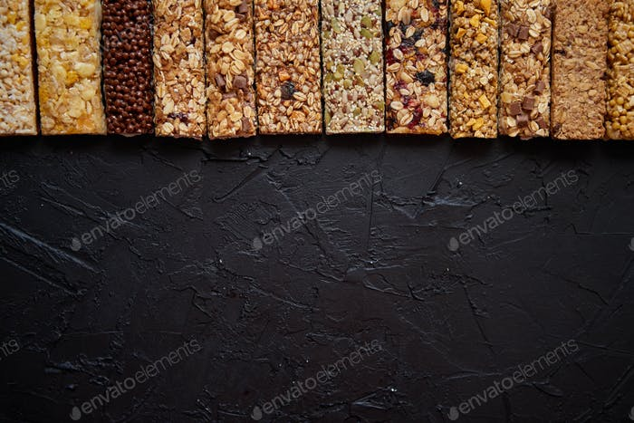 Various healthy granola bars placed in a row on black stone table