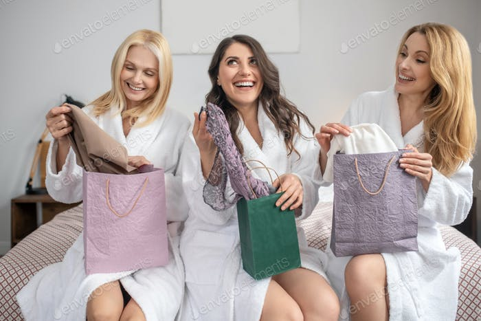 Rejoicing women unpacking their purchases