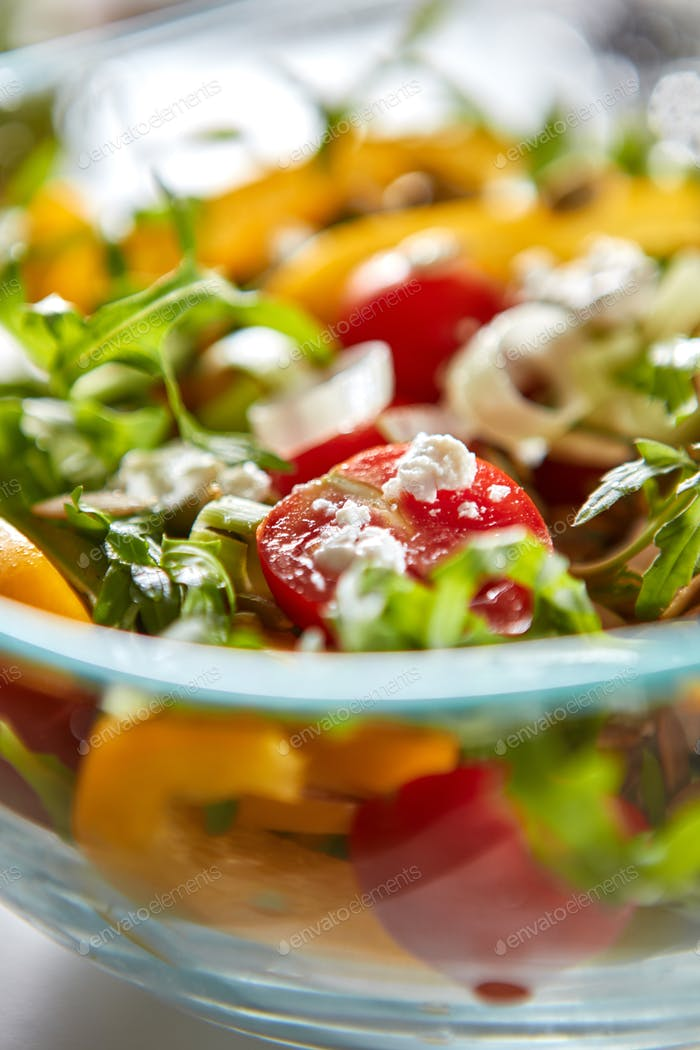 Macro photo of freshly prepared vegetable salad of cheese in a transparent bowl. Healthy vitamin