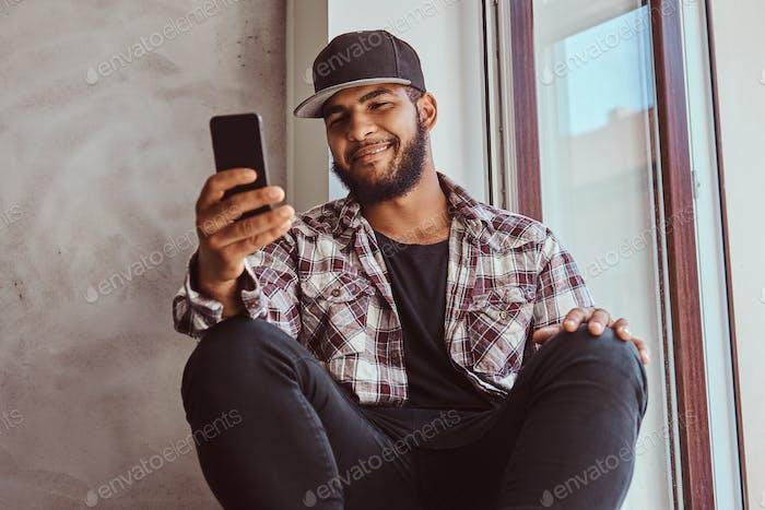 Afroamerikanischer bärtiger Kerl, der im sozialen Netzwerk plaudert.