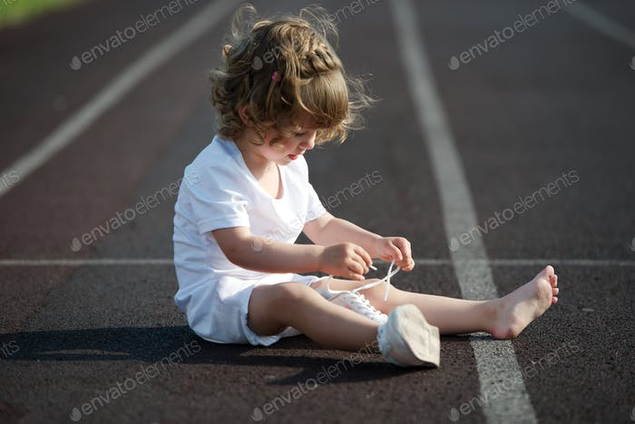 beautiful little girl learning to tie shoelaces