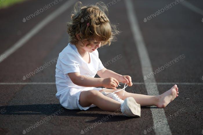 schöne kleine Mädchen lernen Schnürsenkel binden