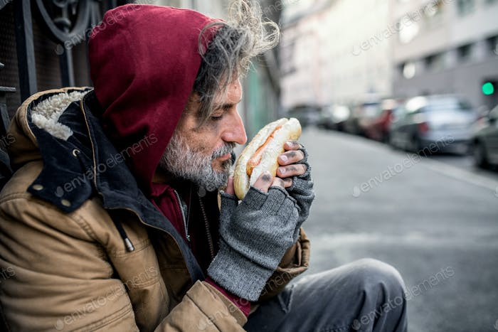 Homeless beggar man outdoors in city, holding and smelling hot-dog.