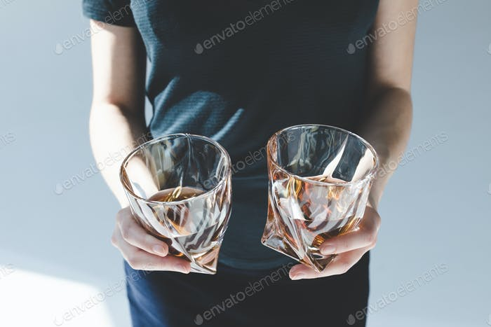 close-up partial view of person holding glasses with luxury brandy