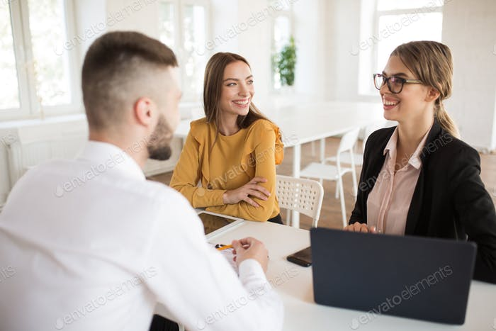 Two cheerful business women happily talking with male applicant