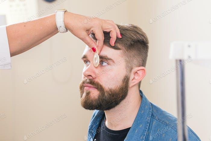 Konzept der Medizin, Gesundheit, Augenheilkunde - Augenarzt untersucht die Augen des Patienten