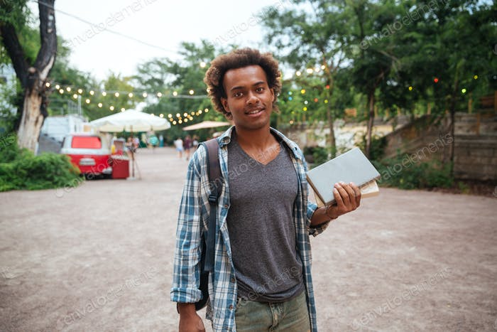 Smiling man with backpack standing and holding books outdoors