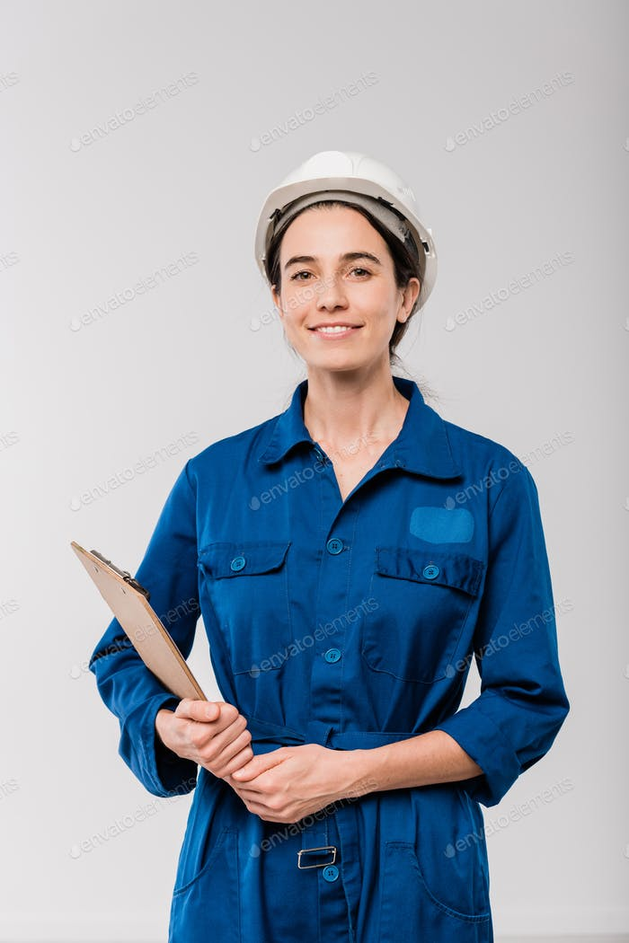 Happy young female mechanic in blue workwear and hardhat holding clipboard