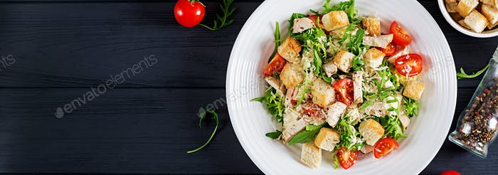 Healthy grilled chicken Caesar salad with tomatoes, cheese and c