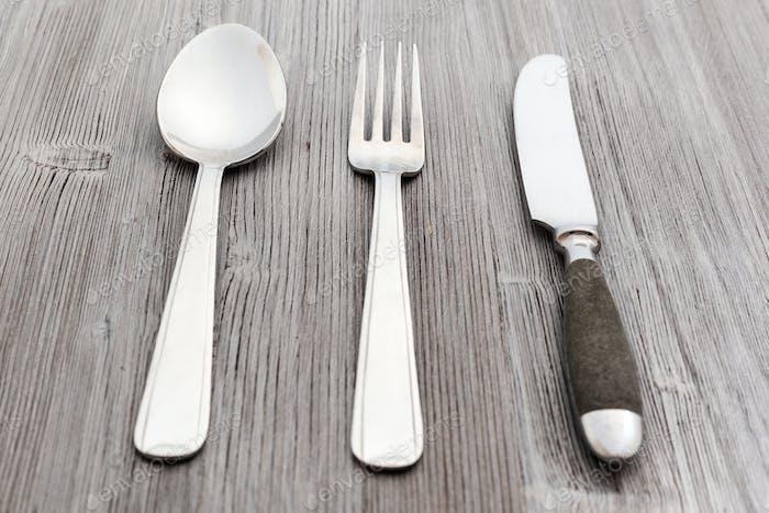 Besteckset aus Messer, Gabel, Löffel auf Holzbrett