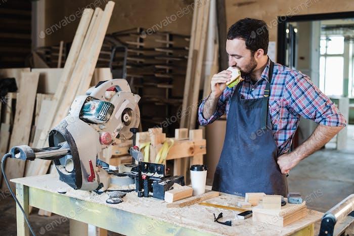 Fröhliche Zimmerei Arbeiter mit Mittagessen essen Sandwich in einer Werkstatt