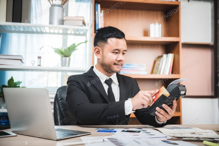 Businessman paying by credit card with a credit card reader machine