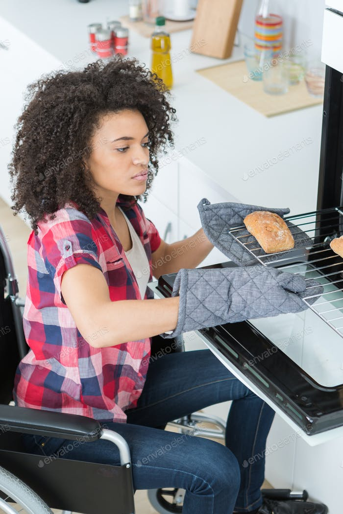 disabled woman in wheelchair putting bread in the oven