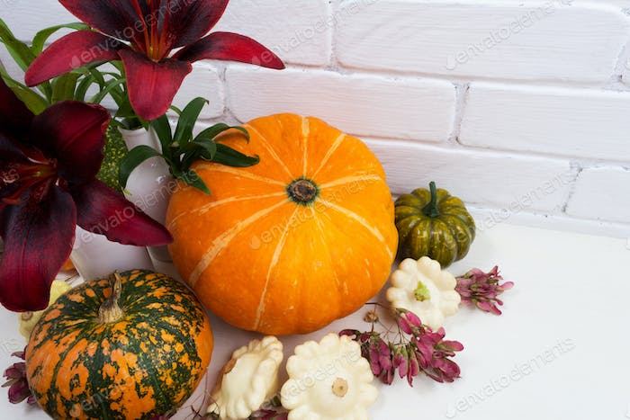 Fall arrangement with red lily and pumpkins