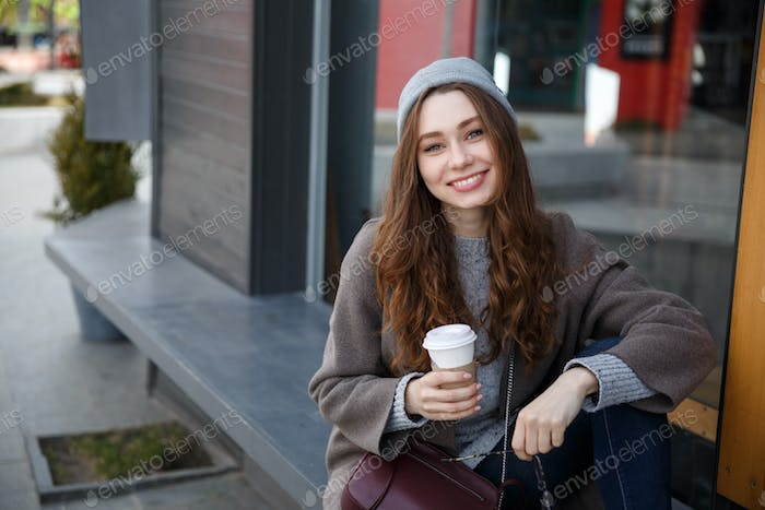Cheerful woman sitting and drinking coffee-to-go in the city