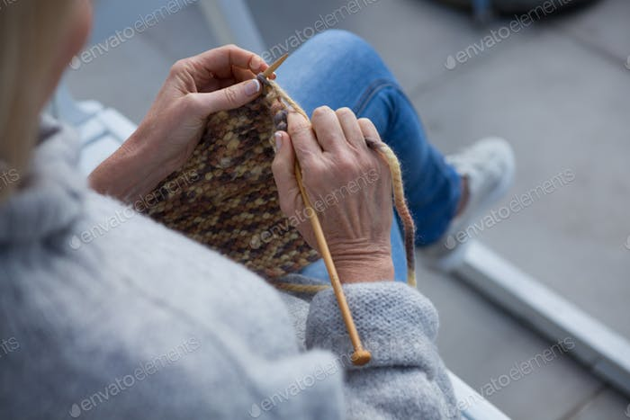 Woman knitting wool in porch