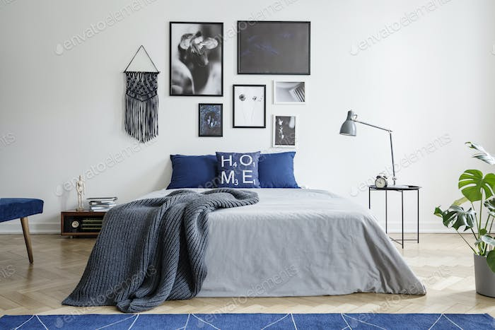 Blanket on bed with blue pillows in white bedroom interior with