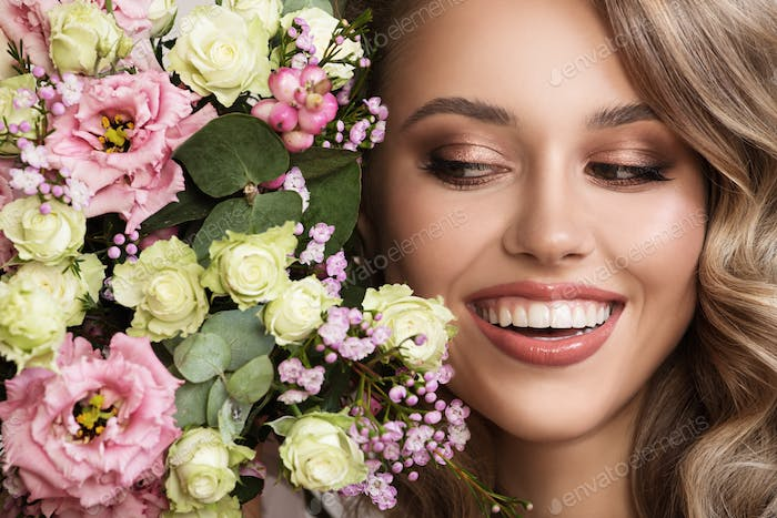 Close Up Portrait Of Beautiful Smiling Woman. Flowers Near Face