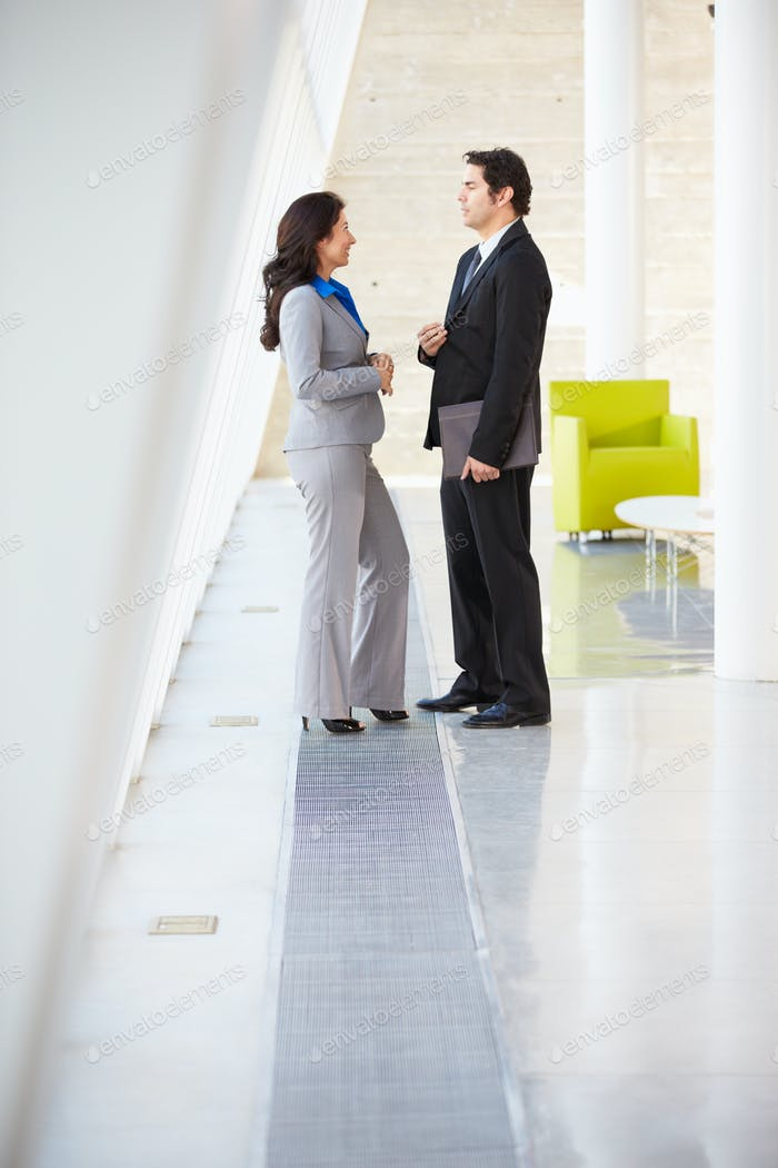 Businessman And Businesswomen Talking In Modern Office