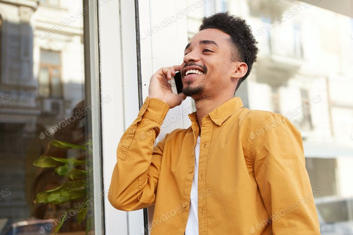 Photo of young African American glad man, walking down the street and talking on the phone