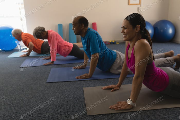 Side view of young female trainer exercising with senior people in fitness studio