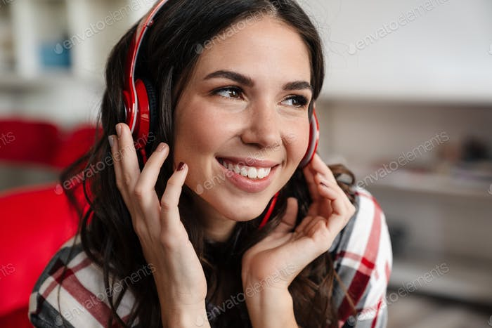 Happy nice woman listening music with headphones and smiling
