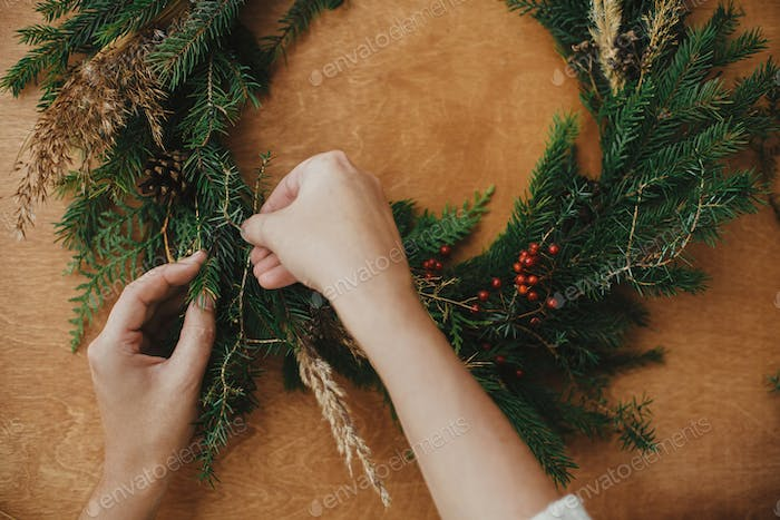 Making rustic Christmas wreath flat lay. Hands holding fir branches