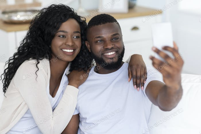 Happy black couple taking selfie with smartphone at home