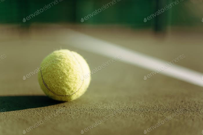 Tennis ball on ground coverage closeup
