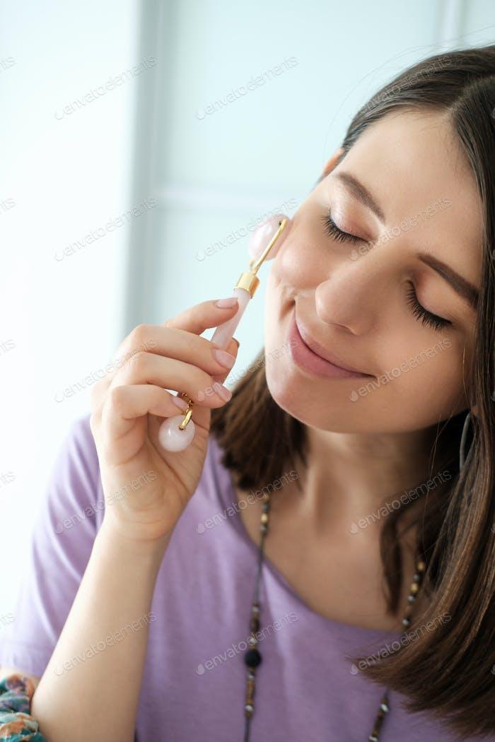 Woman holds rose quartz facial roller