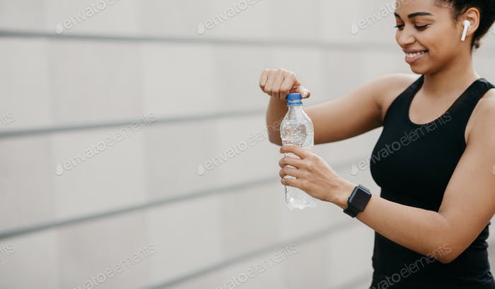Water, healthy lifestyle and outdoor exercise. Smiling african american young woman with wireless