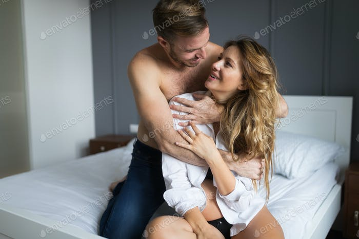 Romantic couple in bed during sexual foreplay