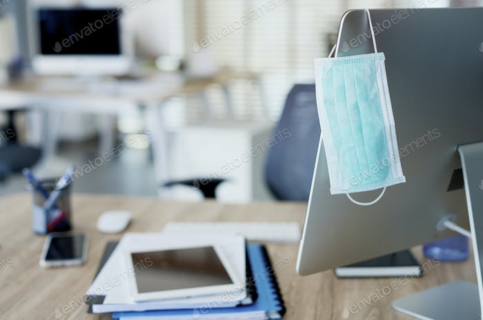 Face mask hanging on computer screen in an empty office