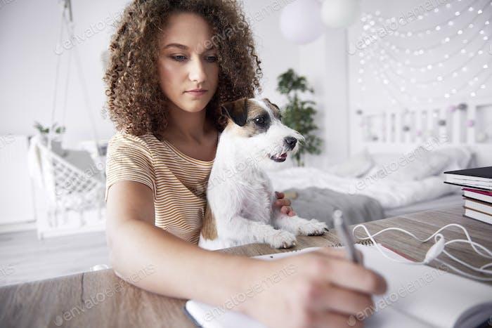 Teenager-Mädchen und ihr Hund studieren zusammen